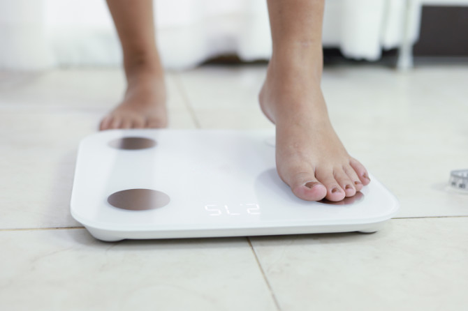 feet standing on electronic scales for weight control. Measureme